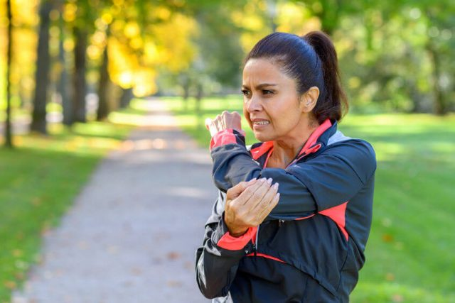 older woman holding a painful elbow after exercising