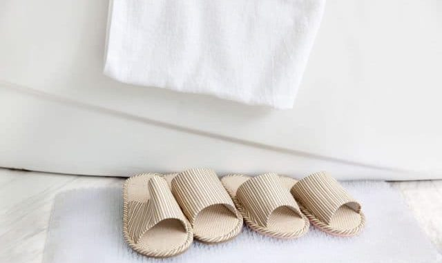 bath mat and bath slippers next to a bath tub