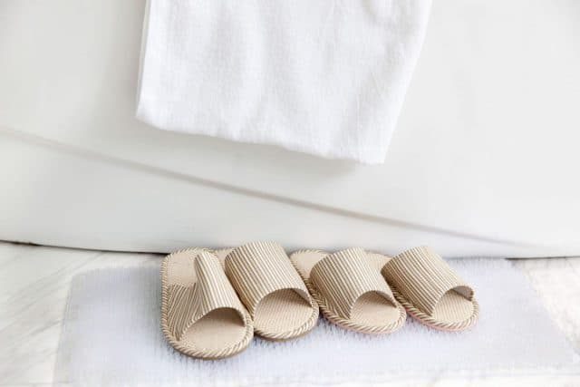 bath mat and bath slippers next to a bath tub