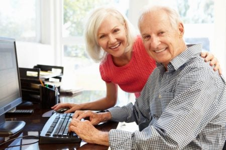 senior man and woman smiling while using a large computer keyboard