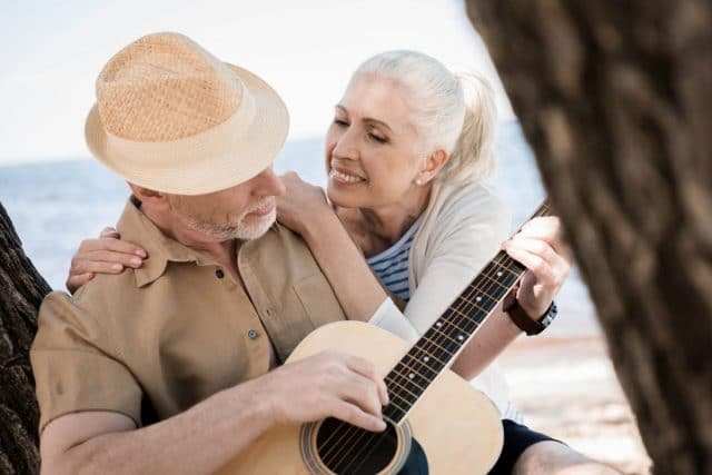 senior man leaning against a tree playing a guitar while his wife looks at him