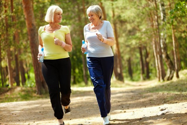senior women running and chatting in the park with water bottles in their hands