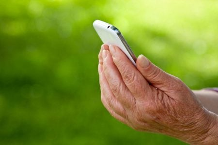 senior holding a cellphone looking at their apps