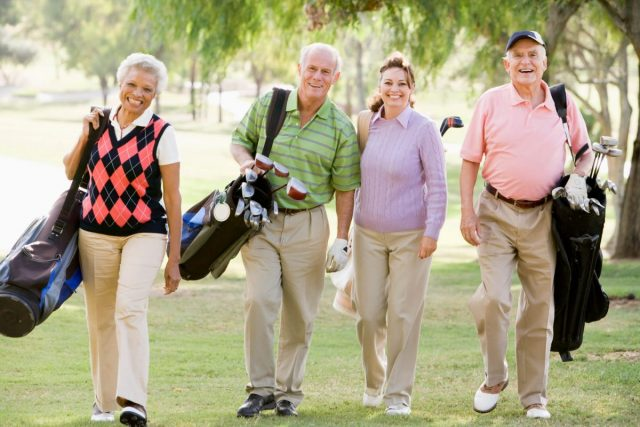senior men and women walking on a golf course with golf bags and clubs on their back