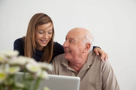 senior man using a laptop with his granddaughter