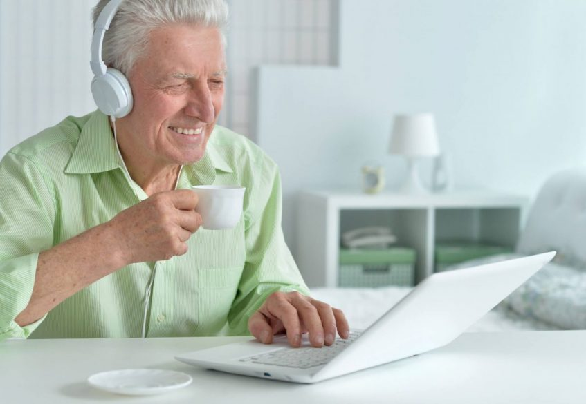 senior manusing TV headphones and enjoying a cup of coffee