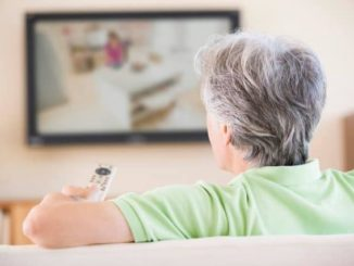 senior man using the best universal remote control to change his TV channel