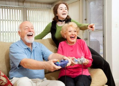 senior couple on a couch playing video games with their granddaugher