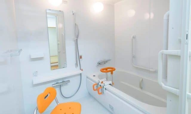 shower chair next to the tub in a clean white bathroom