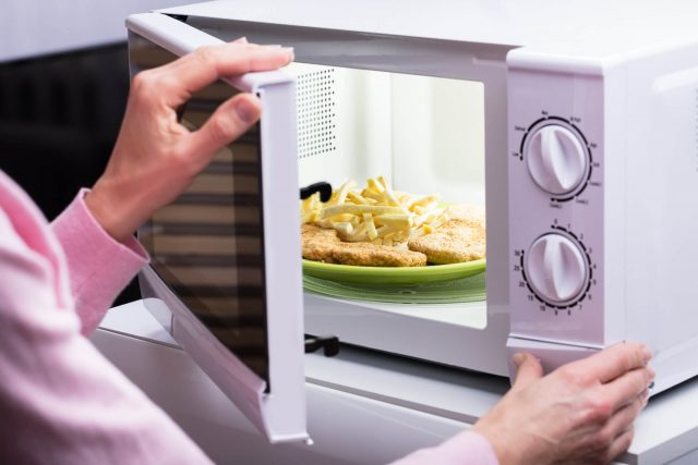 senior woman opening the microwave and removing her food