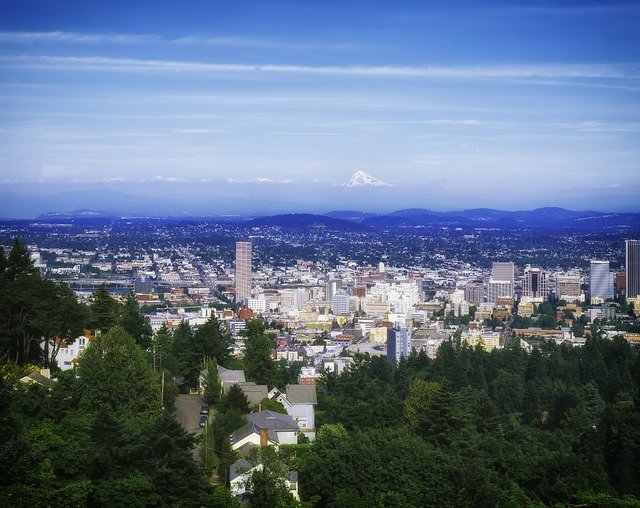 Downtown Portland Oregon viewed from a mountain top with snow capped mountains in the background