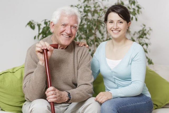 senior man smiling on a couch with his caregiver