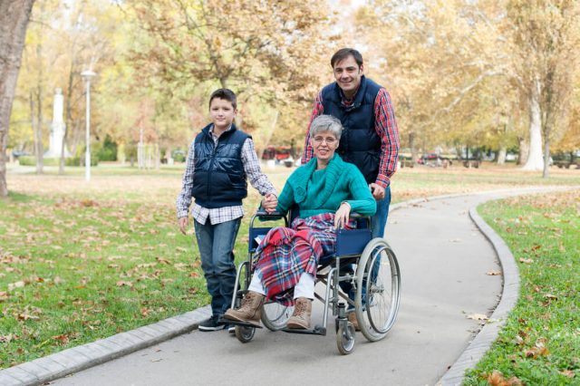 family pushing their grandmother in a manual type of wheelchair