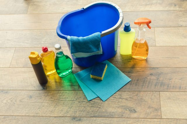 blue bucket with spray cleaners, rags, and a sponge