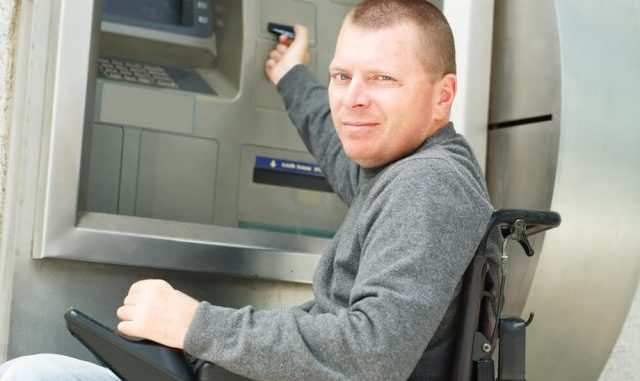 man using a portable power chair at an atm