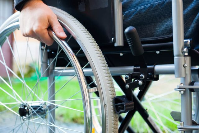 close up of a wheelchair wheel and wheel lock