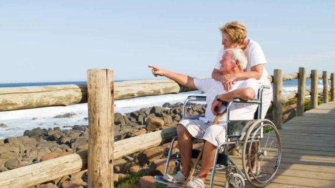 senior couple with limited mobility on vacation at beach