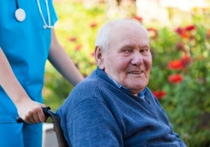 senior man sitting in a rollator transport chair and smiling