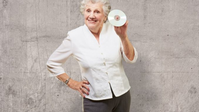 senior woman posing and showing off a CD in her hand