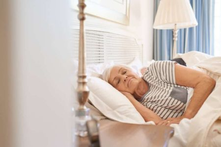 lady using bed step stool for elderly to get in bed safely