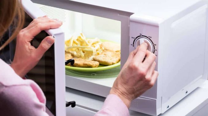 senior woman using a simple microwave with knobs