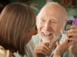 senior man showing his daughter his cordless phone