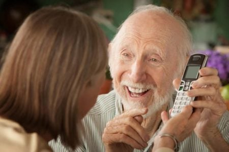 woman giving her senior father a new cordless phone