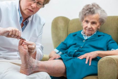 senior lady having her nails cut by nurse