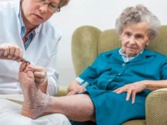 senior lady having her nails cut by nurse