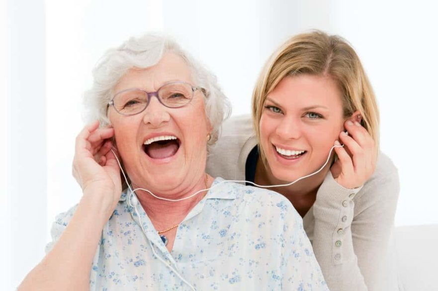 senior woman listening to mp3 player with daughter