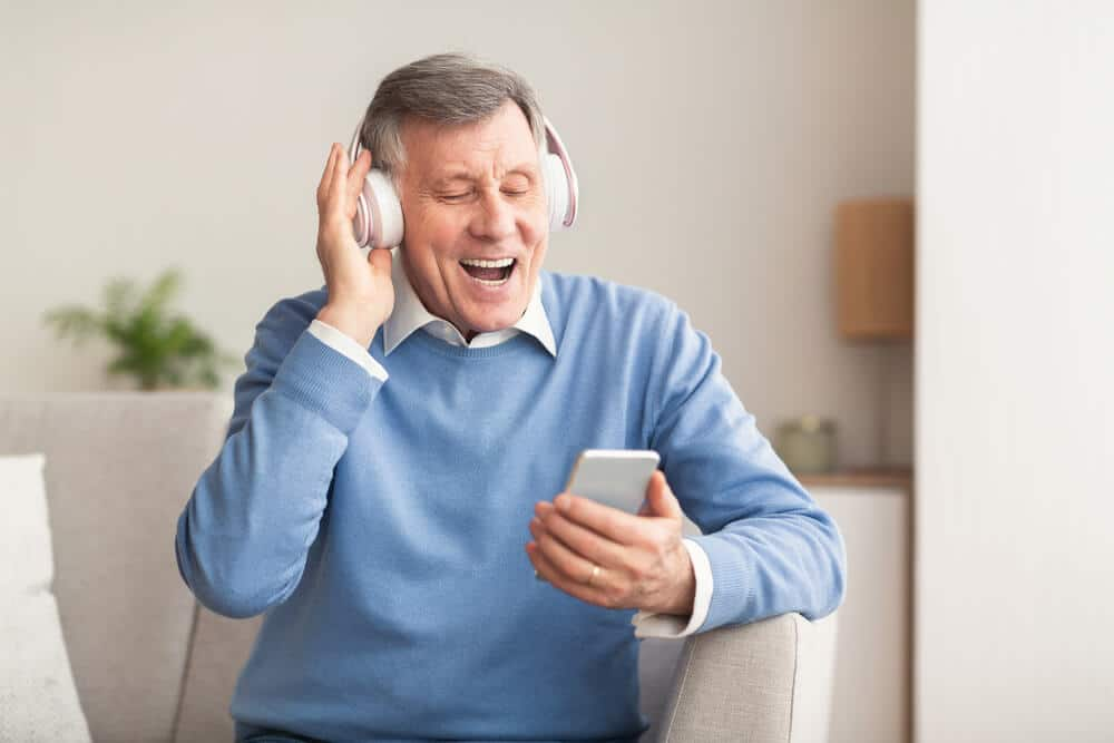 senior man holding a music player and wearing headphones