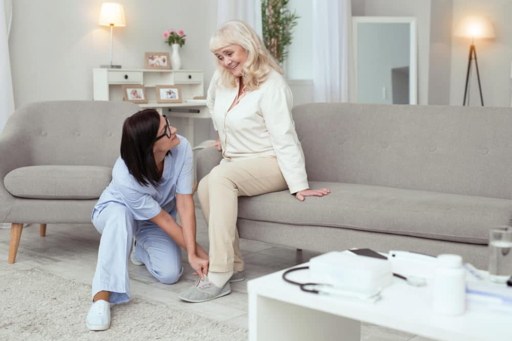 caregiver helping senior woman put on safe slippers