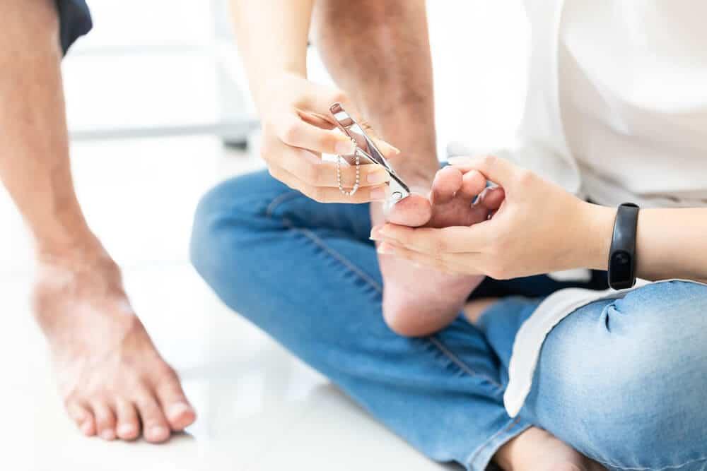 woman cutting her senior mother's toenails
