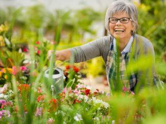 senior woman watering flowers in her garden