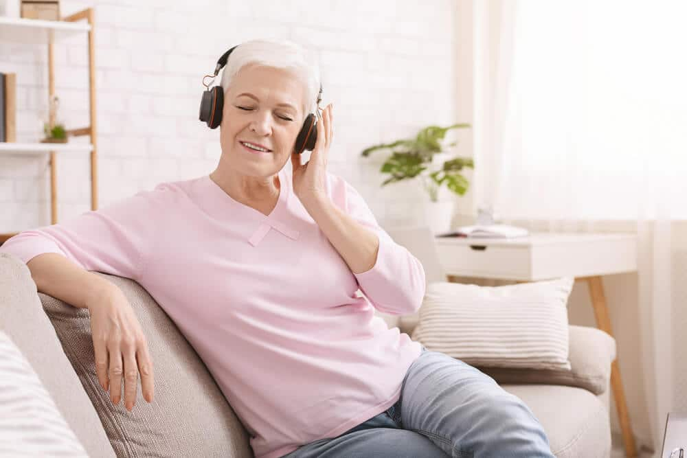 senior woman listening to audiobook in headphones