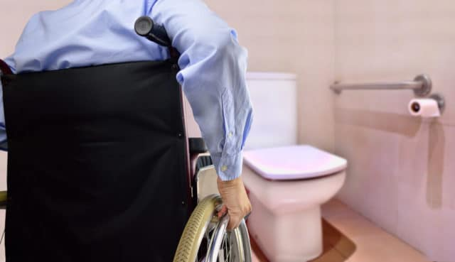 man in wheelchair using a tall toilet for the elderly because it is easier to transfer to