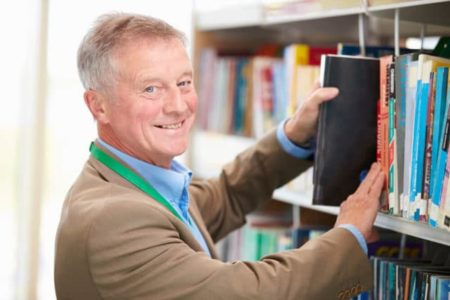 senior man with easy job at the library