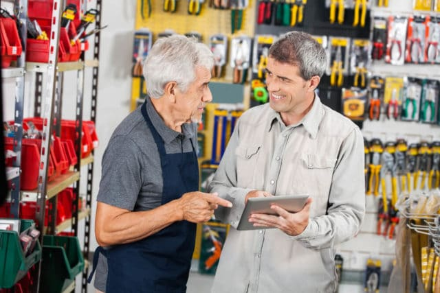 senior man helping a customer in a retail hardware store