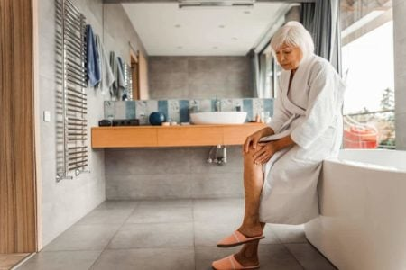 senior woman getting in bathtub