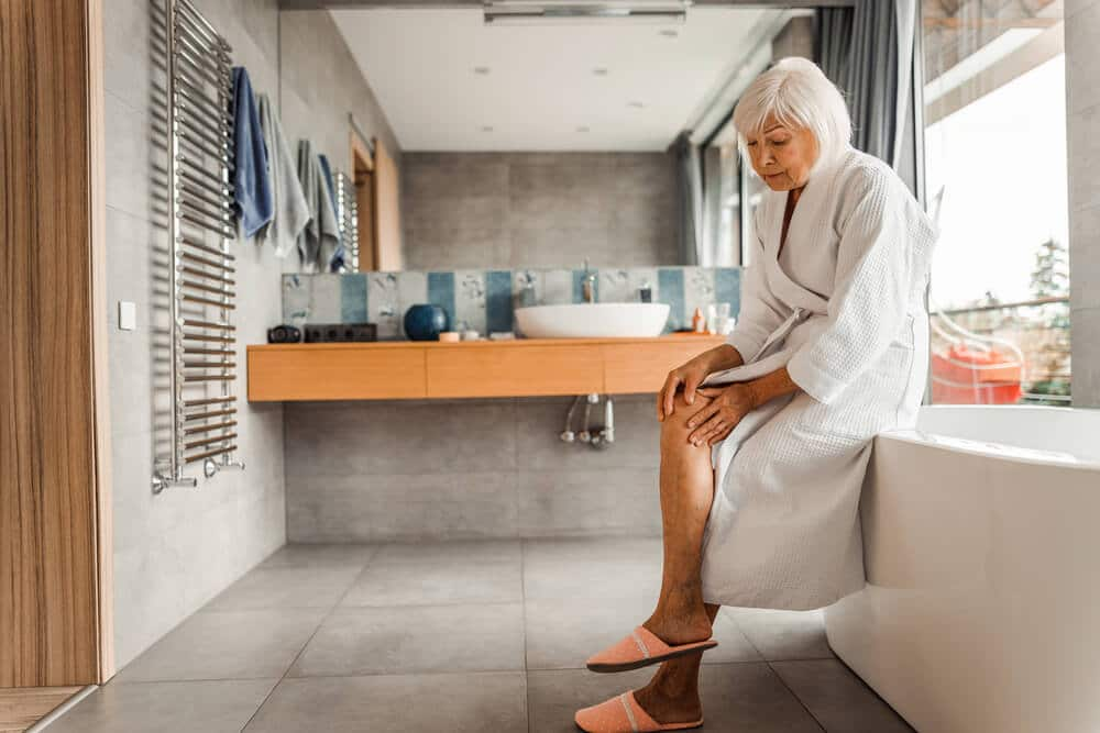 senior woman getting in bathtub