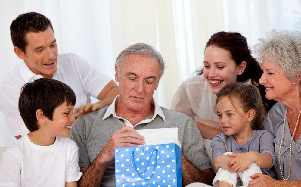 65 year old man opening gift from family