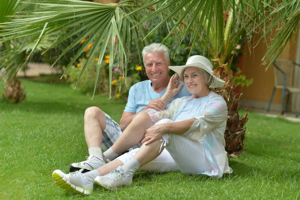 seniors under a palm tree at an all-inclusive resort