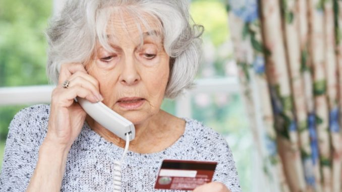 senior woman using phone to place an order with credit card in her hand