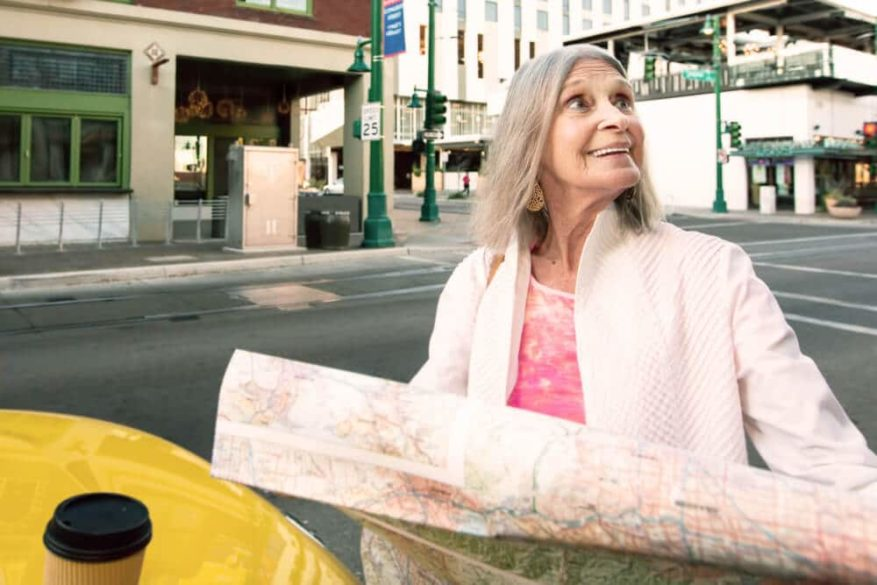 older lady holding a map on tour for seniors traveling alone