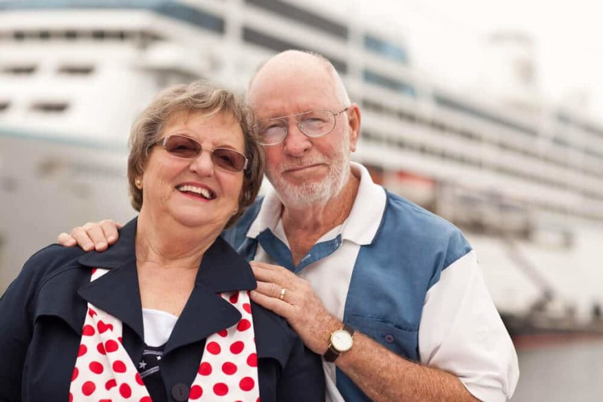 senior couple posing in front of a cruise ship