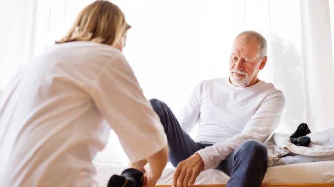 caregiver putting on compression socks for elderly man