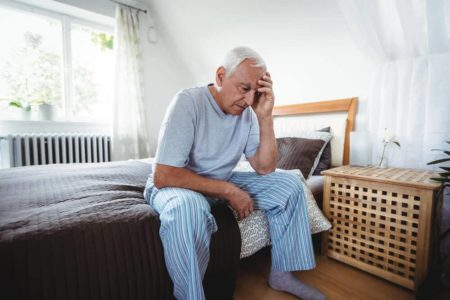 depressed elderly man sitting on his bed