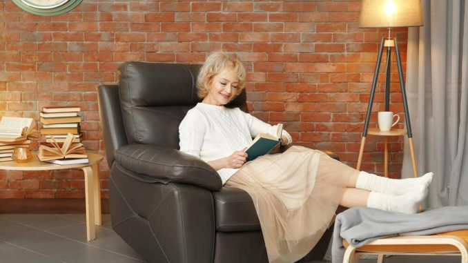 happy senior woman wearing warm socks for seniors with her feet up on a stool
