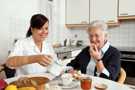 live in caregiver helping senior woman with breakfast