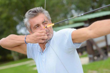 senior man aiming a bow and arrow